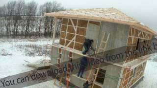 Time-lapse of construction house of straw bales. installing cladding panels on the wall on the
